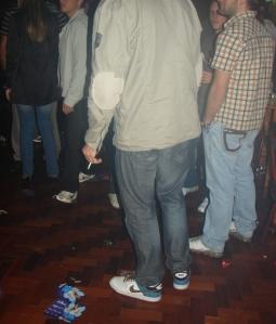 O primeiro, apesar de muito bonito, para a balada não caiu bem, pois demonstra o peso e o domínio da roupa sobre o rapaz. O casaco de sarja estava próprio para uma noite de chuva, porém, na festa, não seria nada mal dispensá-lo juntamente com o cachecol de flanela. A comparação pode ser dada de forma clara e direta, é só olharmos para o look ao lado, uma camisa xadrez de manga curta e uma calça jeans, básico, mas o rapaz aproveitaria a festa tranquilamente.
