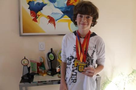 Gui guarda cada medalha e, ao fundo, pode-se ver alguns troféus que seu pai também adquiriu nas competições